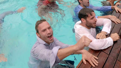 Happy friends playing in the swimming pool Live Action