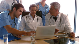 Doctors looking at laptop and discussing Footage