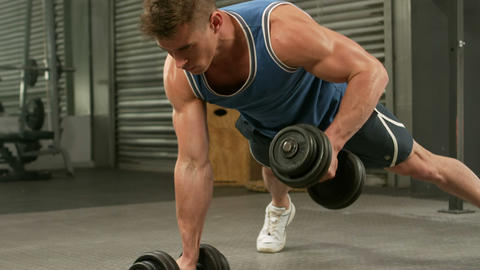 Muscular man doing push ups with dumbbells Footage