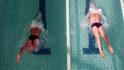 Above view of swimmers diving into pool Footage