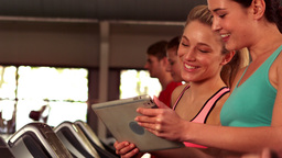 Fit women looking a tablet while fit people running on treadmills Live Action