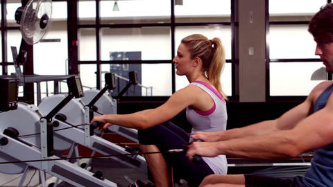 Fit people using rowing machine Stock Video Footage