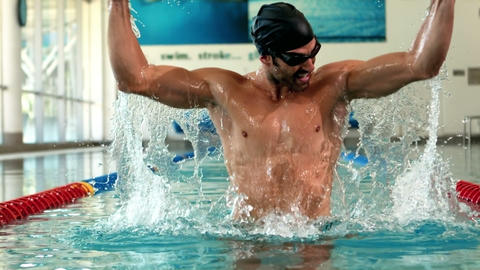 Fit man raising arms in the pool Live Action