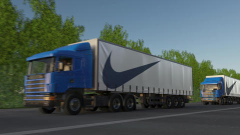 Freight semi trucks with Nike inscription and logo driving along forest road Image