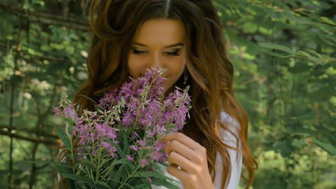 A beautiful sexy girl is holding a bouquet of wildflowers in her hands. It's a Footage