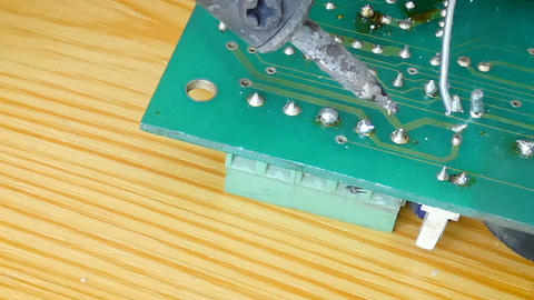 4K Close up shot electric solder in soldering on electronic print circuit board Footage