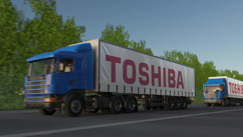 Freight semi trucks with Toshiba Corporation logo driving along forest road Footage