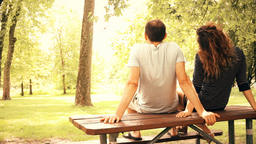 Back of young couple sitting on top of picnic table in outdoor park sunbathing Footage
