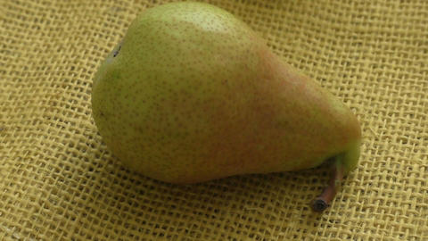 Ripe pear on yellow background. European pear with sack cloth Footage