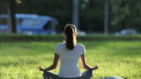 Woman meditates in the park against the background of traffic Acción en vivo