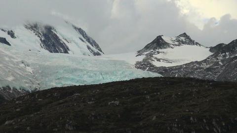 Birds fly in front of blue glacier Footage