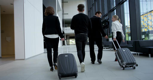 Business people walking with wheeled bags Footage