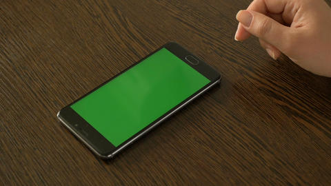 A female hand and a mobile phone with a green screen that lies on the table Archivo
