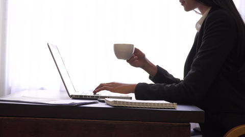 Hands typing keyboard and holding coffee cup,successful business woman working Footage