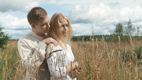 Young blond woman and her boyfriend are hugging on the field with wheat Image