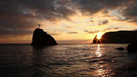 Cross on a rock in the sea, on the coast in the evening ビデオ