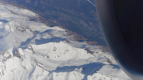 Operating jet engine of the airplane and distant alpine town Footage