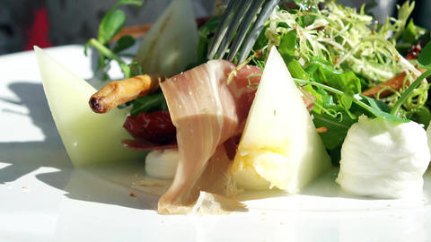 Eating lettuce, melon and ham salad at the restaurant Footage