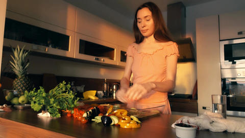 Beautiful young woman cooking vegetable dish at home Footage