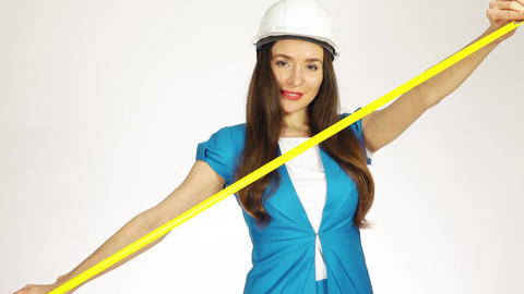 Beautiful female construction engineer or architect using measure tape Footage