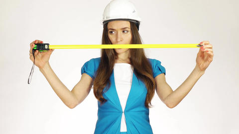 Beautiful female construction engineer or architect in hard hat using measure Footage