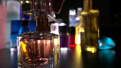 Woman opens small bottle and sprays perfume in the dark Footage