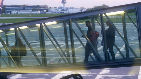 Passengers walking in a glass jet bridge Footage