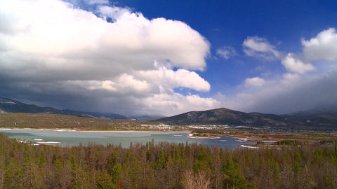 Shifting clouds over mountainside pond Footage