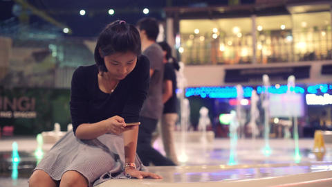Young asian woman resting near fountain on night street Footage