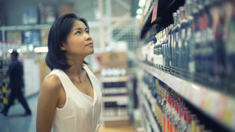Young Asian lady choosing alcoholic beverage in hypermarket Footage
