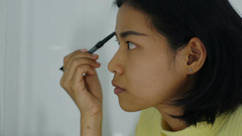 Young Thai Woman shaping her eyebrows with cosmetics pencil Footage