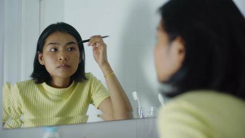 Woman applies cosmetics to her eyebrows in front of mirror Footage