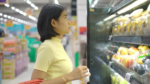Asian Girl shopping for fruits and vegetables in grocery shop Footage