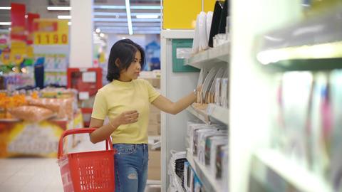 Young Asian Woman choosing tableware in crockery department Footage