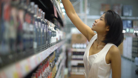 Young Thai Woman picking alcohol in hypermarket Footage