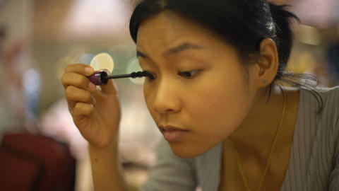 Young Asian Lady applying mascara on her eyelash Footage
