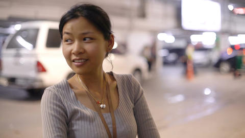 Smiling Asian woman in underground car parking Footage
