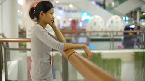 Young Thai Lady talking on smart phone in shopping mall Footage