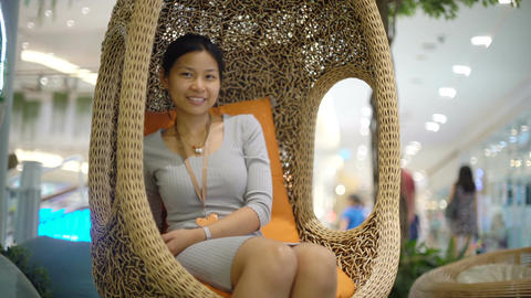 Attractive Asian Woman sits on wicker chair in shopping mall Footage