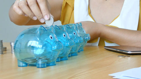 Hands of woman putting money coin into clear piggy bank with blank paper tag Footage