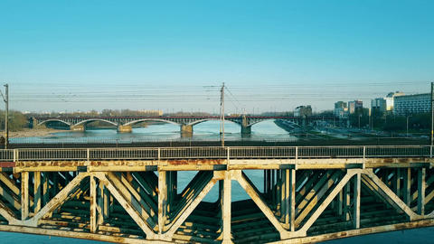 Aerial shot of old steel railway and distant car bridges across the river Footage