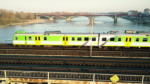 Green and yellow passenger train moving on railway bridge across the river Footage