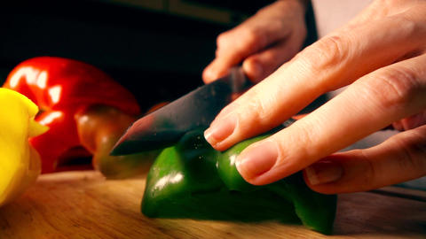 Young woman cutting juicy green sweet pepper Footage