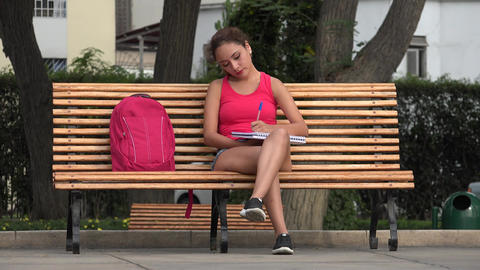 Female College Student Writing In Notebook Sitting On Park Bench Live Action