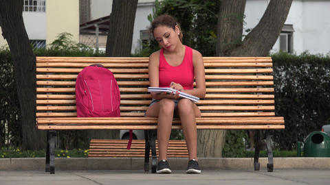 Female Student Studying And Reading On Park Bench Live Action
