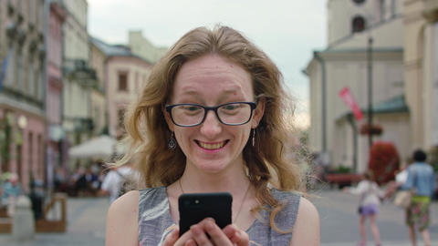 A Beautiful Redhead Using a Mobile Phone Outdoors Footage