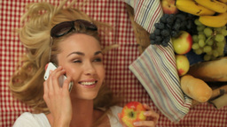 Woman on a picnic chatting on a phone Stock Video Footage