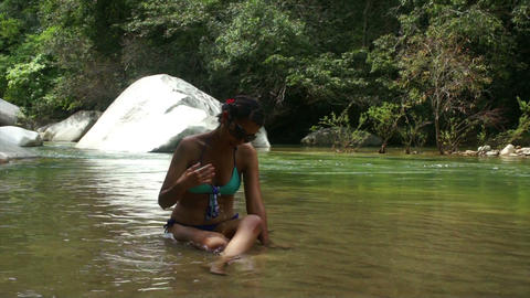 Woman sitting in a river Stock Video Footage
