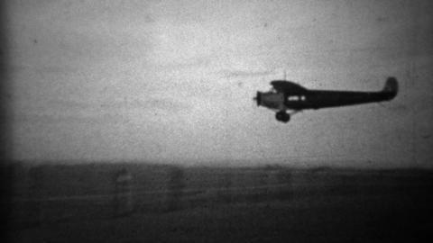 1934: Propeller plane landing in primitive airport landing strip Footage