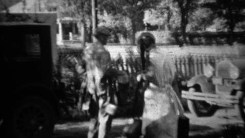 1934: Couple packing up Ford model A car for fishing camping trip Footage